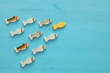 Leadership concept with swimming fish on wooden background. One leader leads others.