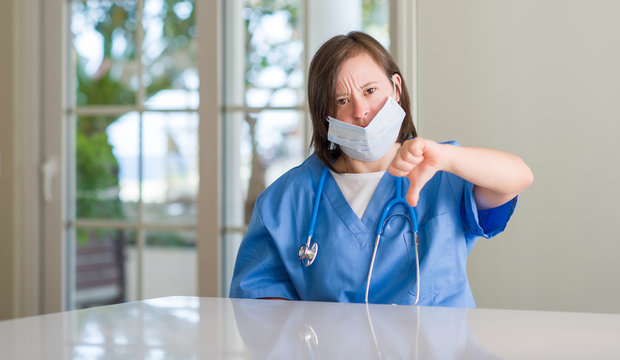 Down syndrome woman wearing nurse uniform with angry face, negative sign showing dislike with thumbs down, rejection concept