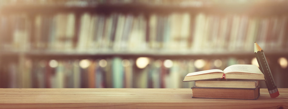back to school concept. stack of books over wooden desk in front of library.