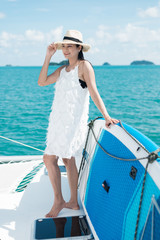 Lifestyle series: Asian woman relaxing on catamaran yacht with SUP board in the background