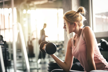 Sport Woman Lifting Dumbbells and Workout Exercises in Gym - Lifestyle and Healthcare Concept