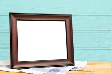 Picture frame put on wooden table in blue wood wall room.