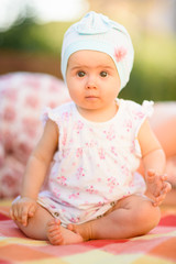 Beautiful infant baby girl on blanket on green grass looking towards camera with big round eyes