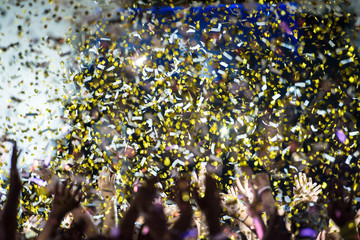 Thousands on confetti fired during a concert. Silhouette of hands in the air. Happy people