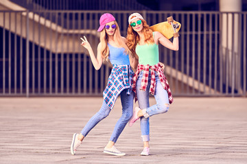 Wall Mural - Street Fashion. Two Girl in Sunglasses Having Fun with Skateboard. Outdoor, Urban background. Cheerful Friend Enjoy Summer day. Young Beautiful caucasian Woman Smiling in Trendy jeans