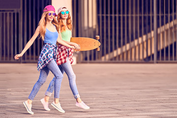 Wall Mural - Two Girl Jump Having Fun with Skateboard. Outdoor, Urban street background. Playful redhead Hipster Friend Enjoy Smiling. Young Beautiful Model Woman in Fashion Trendy Outfit.