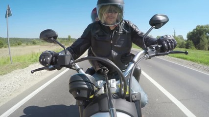 Fototapete - Couple Bikers in a leather jacket riding a motorcycle on the road