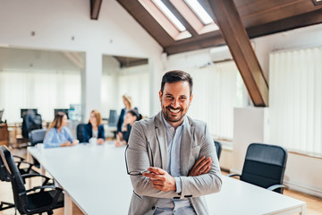 Portrait of a smiling handsome businessman with crossed arms in a meeting room.
