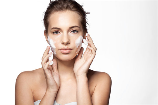 Portrait of young pretty woman applying foaming cleanser on white background. Lovely female with clean fresh perfect skin looking at camera with calmness. Skincare concept.