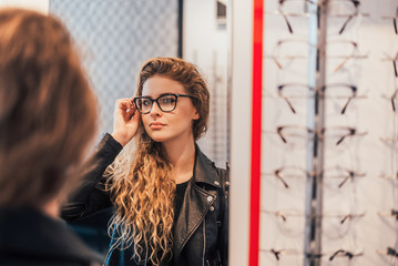 Woman trying new glasses, looking on mirror. Wall mural