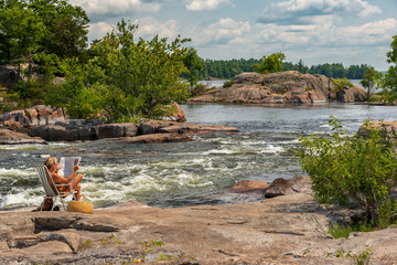 woman sitting on rocky shore of rapids, reading newspaper