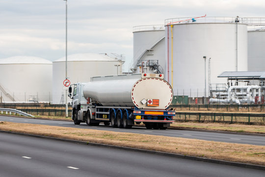 Tanker lorry in motion on the road with oil depot in the background