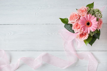 Background with a bouquet of pink roses and gerbera, ribbon