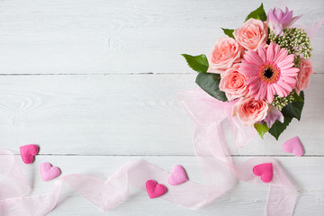 Background with a bouquet of pink roses and gerbera, ribbon and hearts