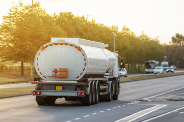 Tanker lorry in motion on the road during sunset
