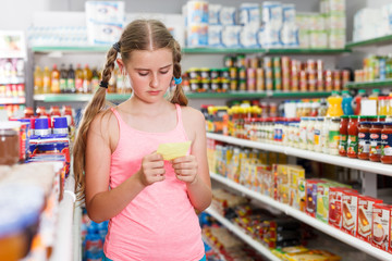 tweenager girl looking at shopping list