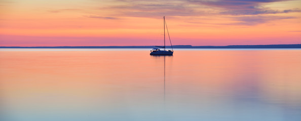 Fototapeten See / Weiher The world at rest - sailing boat in calm lake at sunset