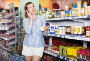 Female with phone choosing mayonnaise at  supermarket
