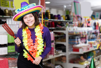 Happy young female having fun in festival outfits store
