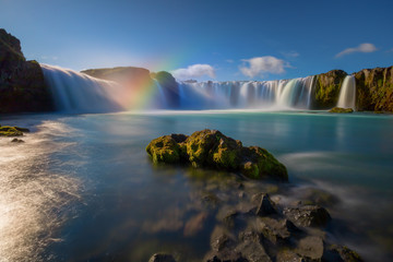 Iceland's Godafoss waterfall on a clear, sunny day.  The falls creating streams of light through the water and a rainbow