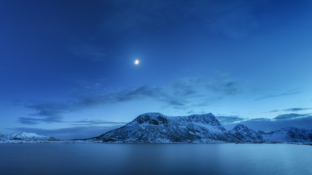 Snow covered mountains against blue sky with clouds and moon in winter at night in Lofoten islands, Norway. Arctic landscape with sea, snowy rocks, moonlight, reflection in water. Beautiful fjord