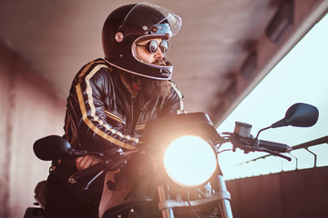 Close-up portrait of a brutal bearded biker in helmet and sunglasses dressed in a black leather jacket sitting on a retro motorcycle with an included headlight.