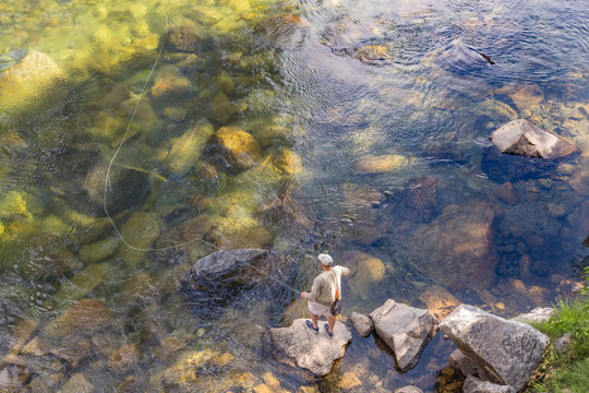 A Man Fly Fishing in a Shady Rock-Filled River