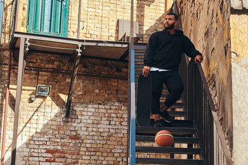 Dark skinned bearded hipster guy dressed in a black hoodie and sports shorts holds a skateboard while standing on stairs in ghetto.