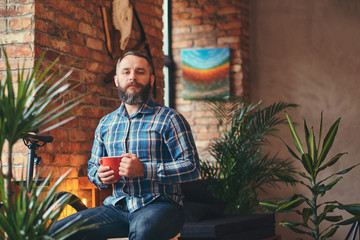 Handsome bearded hipster male in a blue fleece shirt and jeans holds a cup of morning coffee while sitting on a wooden stool at a studio with a loft interior.