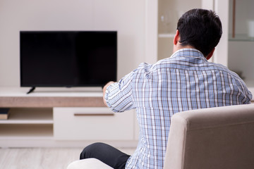 Young man watching tv at home