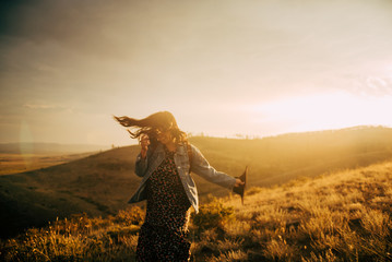 Happy girl walking on field at sunset