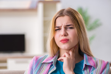 Young woman suffering from sore throat pain