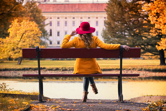Attractive young woman with red hat sitting on a bench in park and enjoying a view on castle at autumn season. Fashion concept