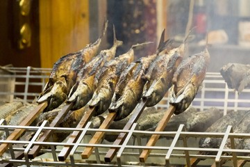 Barbecue stockfish grilled trout fish on stocks with fire smoke. Delicious crispy staple nutrition salmon at a medieval market with succulent flavor and protein