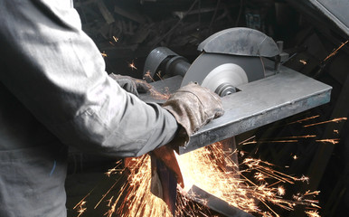 Cutting of metal. Closeup men's hands cutting metal with a circular saw. Sparks fly to the side.