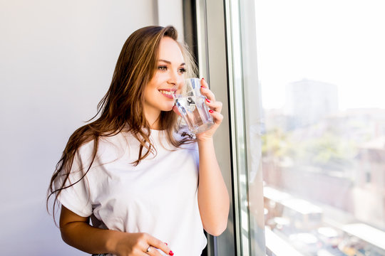 Young Woman holding a glass of water while looking out of the window