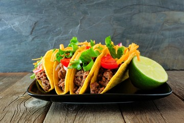 Hard shelled tacos with ground beef, lettuce, tomatoes and cheese. Group on plate with a dark background.