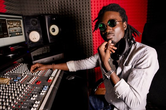 African male adjusts music to sound mixer for recording, broadcasting, background music