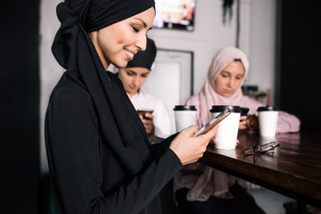 Muslim girl hijab communicates on social networks via phone on background of girlfriends in cafe