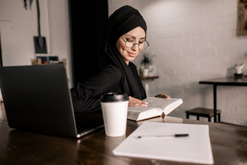Muslim girl hijab reading a book at a table in a cafe