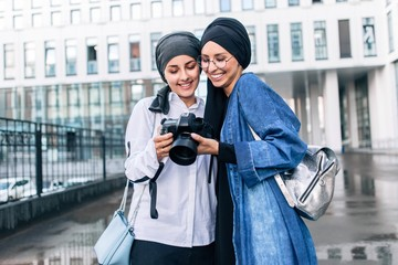 Muslim women hijab view photos on camera standing on the street of the city
