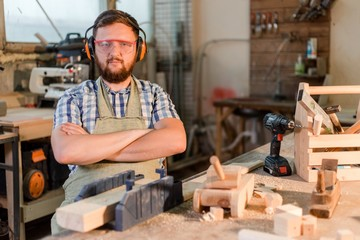 Bearded carpenter in goggles standing in the carpentry workshop with arms crossed