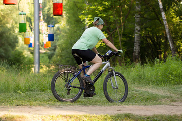 Sports woman cycling in the park. Side view