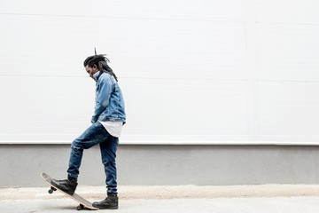 African man with dreadlocks in jeans jacket rides a skateboard on the background of the building
