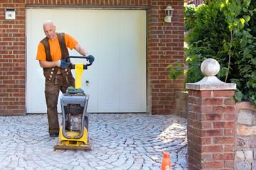 Installation of brick pavers on a driveway.