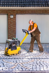 Man using a mechanical compacter on new pavers.