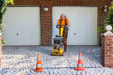 Builder or contractor laying new paving bricks.