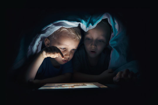 Two kids with tablet computer in a dark room