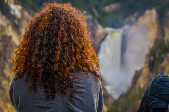 Close up of selective focus of red curly hair of a woman with a blurred background of the upper Yellowstone Falls in Yellowstone National Park, Wyoming, United States