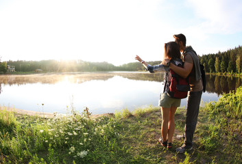 Young couple on shore of beautiful lake, wide-angle lens effect. Camping season Wall mural